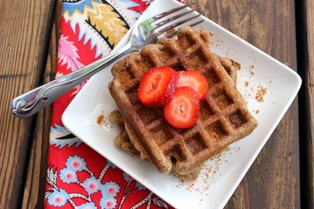 two gluten and dairy free churro waffles on a white plate with fresh strawberries on top with silver fork