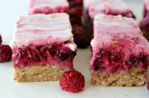 two paleo berry dessert bars with raspberry in front