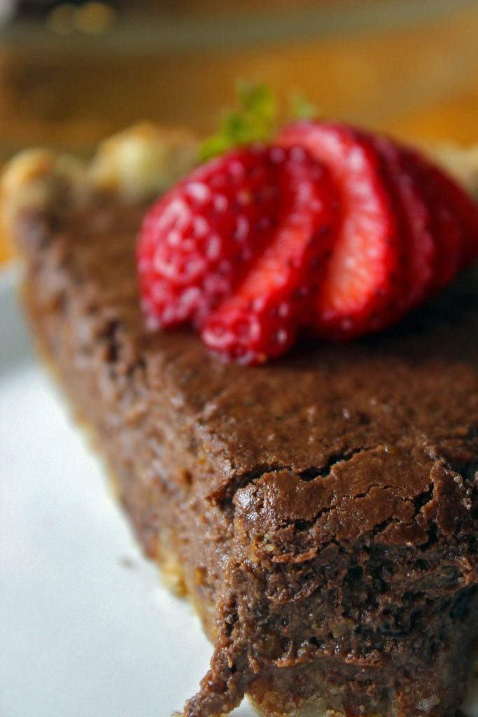 a piece of paleo chocolate pie with strawberry on top on a white plate
