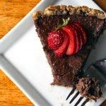 paleo chocolate pie with strawberry garnish on white plate
