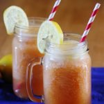 two peach lemonade cocktails with striped straws and lemon wheels on a blue cloth placemat