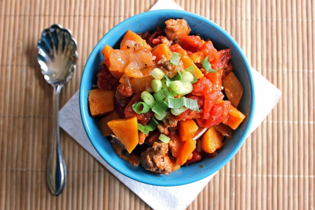 top view of sweet potato chili in a blue bowl on a bamboo placemat with spoon