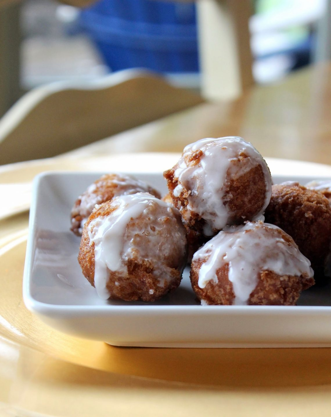 gluten free donut holes with glaze piled on a white plate