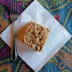 piece of gluten free cinnamon coffee cake on white napkin and colorful placemat