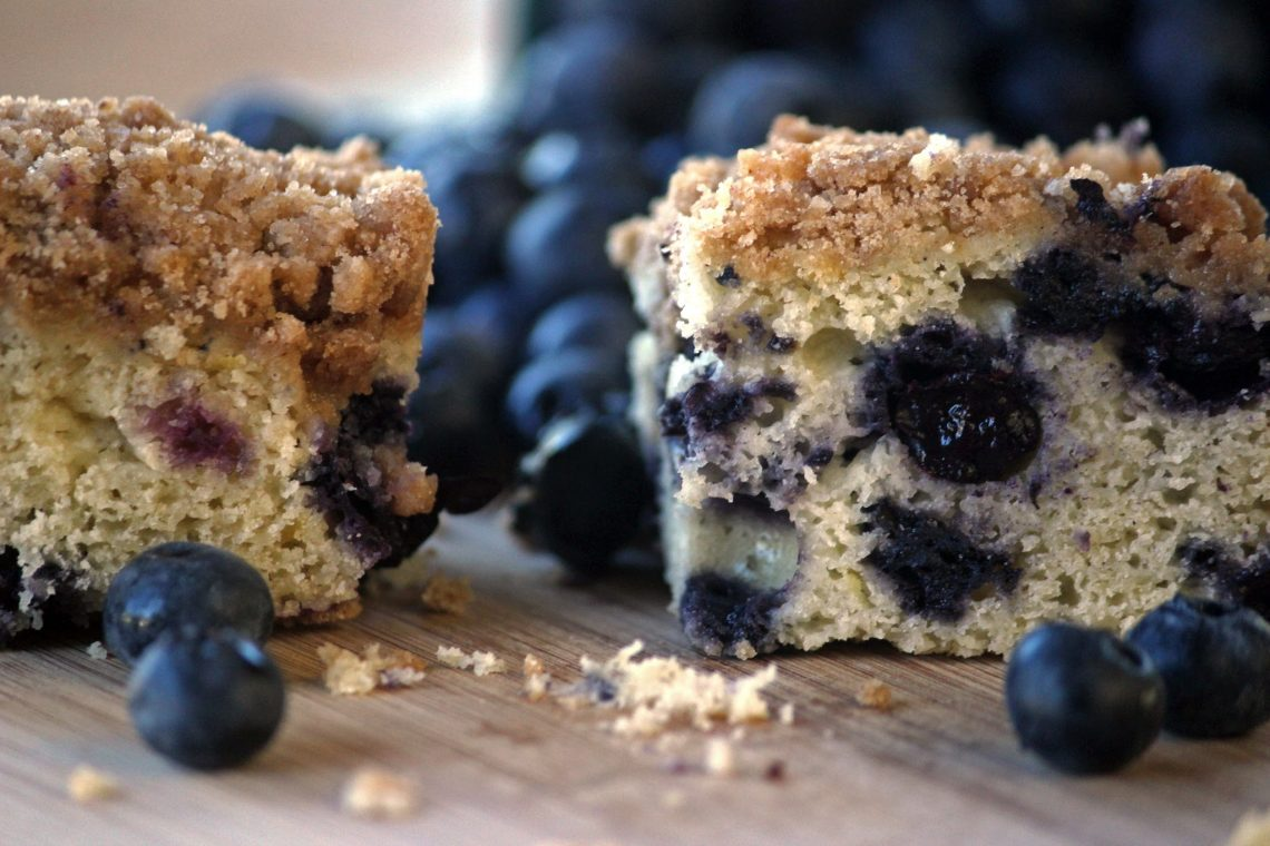pieces of blueberry crumb cake with a pile of blueberries in the background