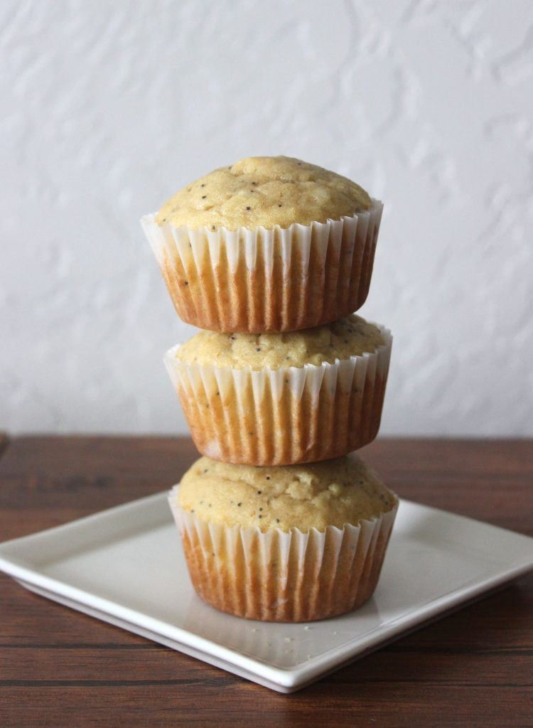 three moist almond poppy seed muffins stacked on top of each other on a white plate
