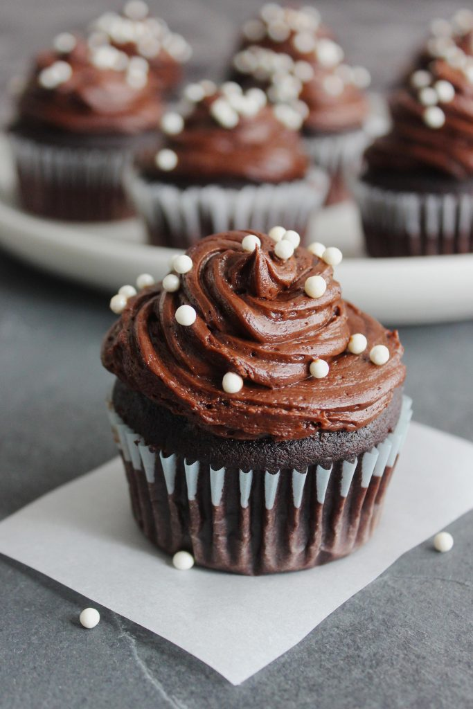 chocolate cupcake with white sprinkles and chocolate frosting