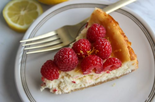 slice of lemon raspberry cheesecake on a white plate with fork