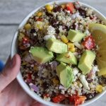 cold quinoa salad in a white bowl with a lemon slice