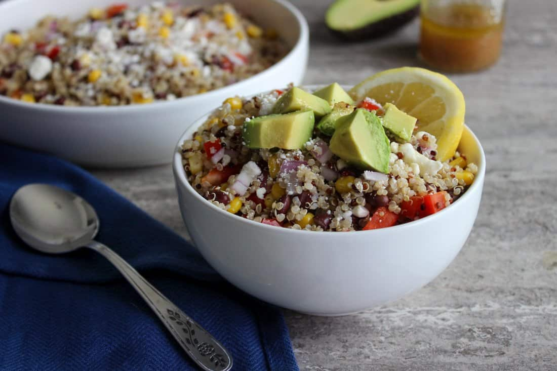 Quinoa salad in a white bowl with a silver spoon next to it