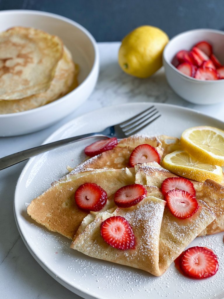crepes with strawberries, lemon wedges on a white plate