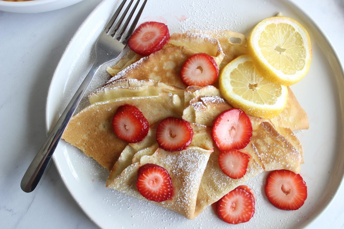 crepes on a white plate with strawberries