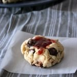 one chocolate chip cookie with strawberry jam on a piece of parchment paper