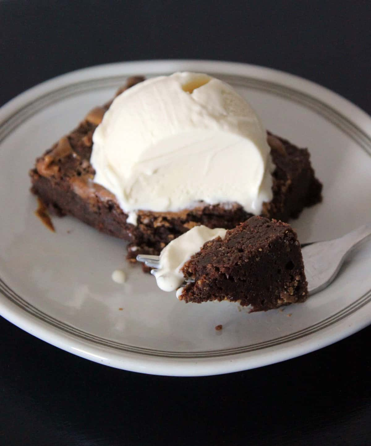 almond butter brownie on a white plate with vanilla ice Crean
