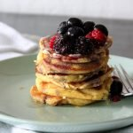 a stack of gluten free pancakes with berries on top