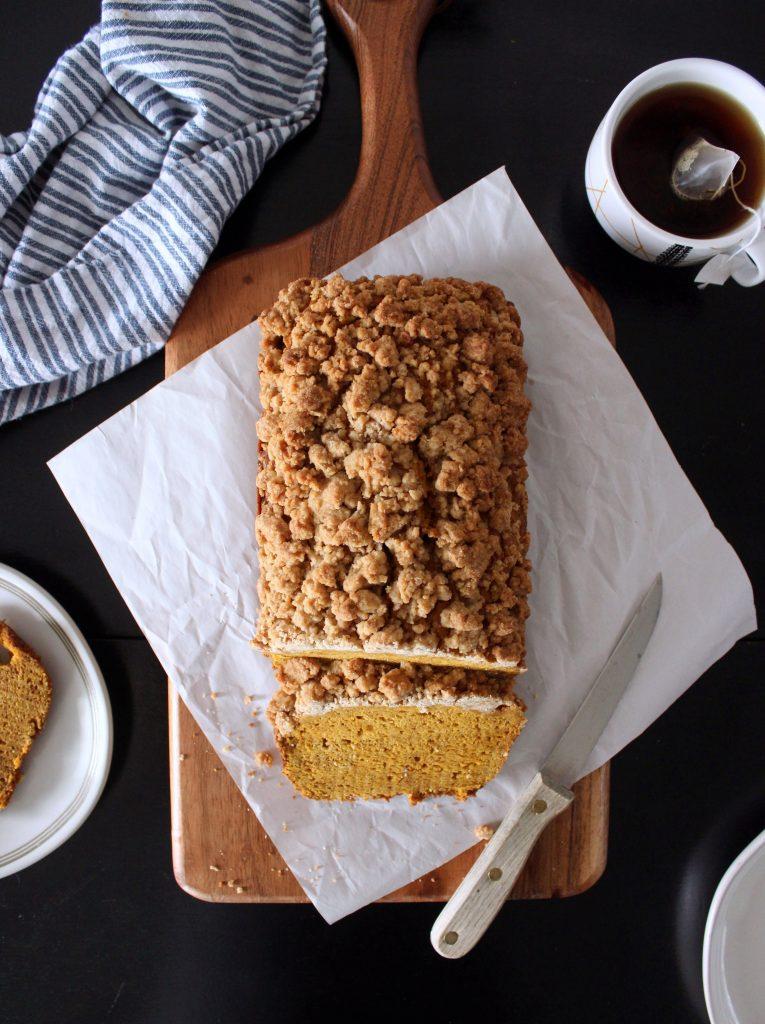 gluten free pumpkin bread load on a cutting board with tea next to it