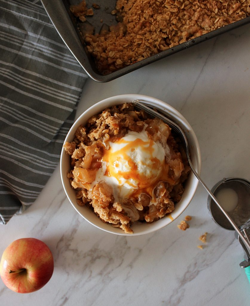 gluten free apple crisp in a white bowl next to a gray napkin and an apple