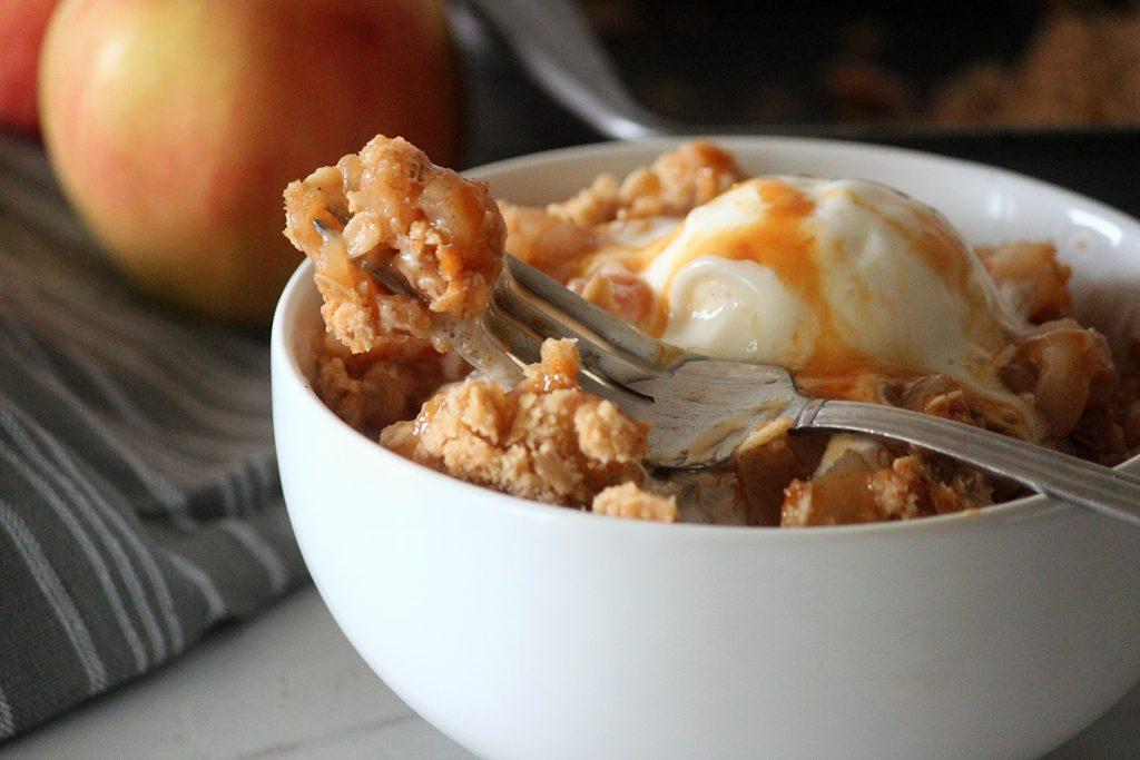 gluten free apple crisp on a fork in a white bowl